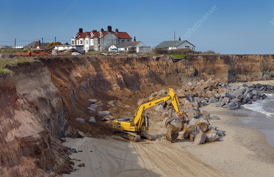 Excavator with grapple used for building sea defences