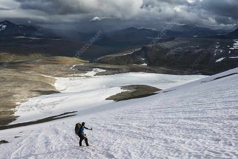 Cross country skier walking on glacier