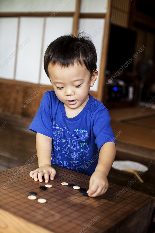 Little boy standing on porch of Japanese house playing Go