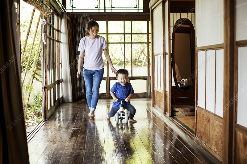 Japanese woman and little boy on a tricycle outside a house