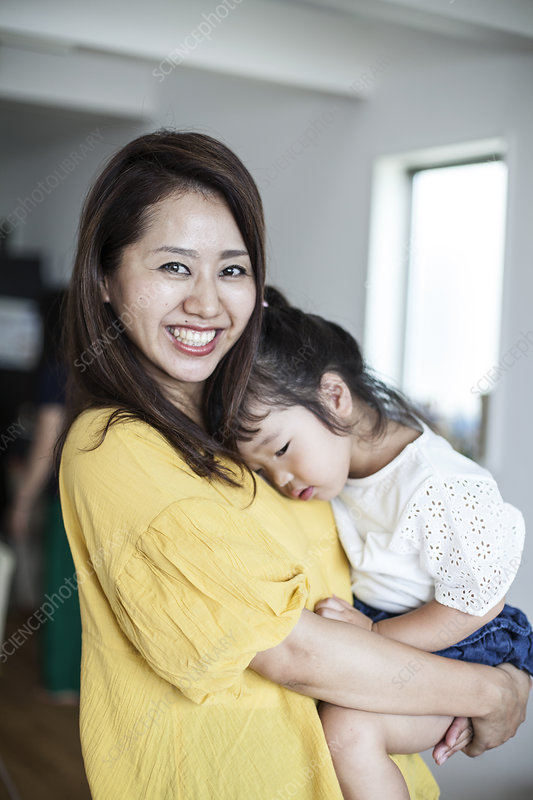 Japanese woman in a living room carrying young girl