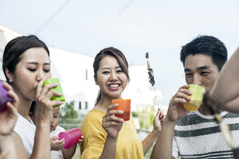 Japanese men and women standing outdoors drinking beakers