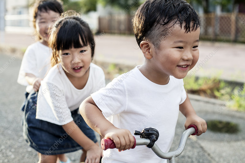 Two Japanese girls and boy playing on street with a bicycle