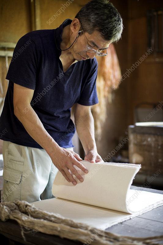 Japanese man checking through sheets of Washi paper