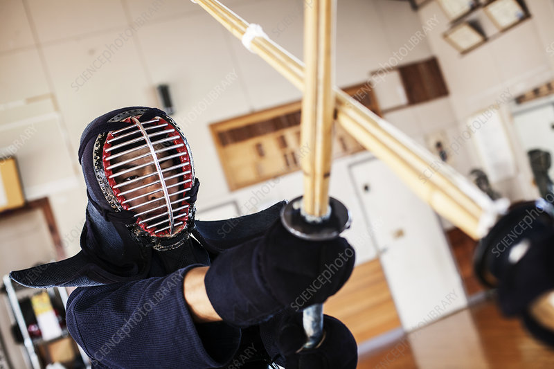 Two Kendo fighters practicing with wood sword in gym