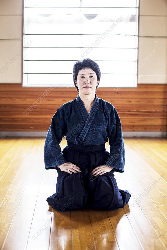 Female Japanese Kendo fighter kneeling on wooden floor