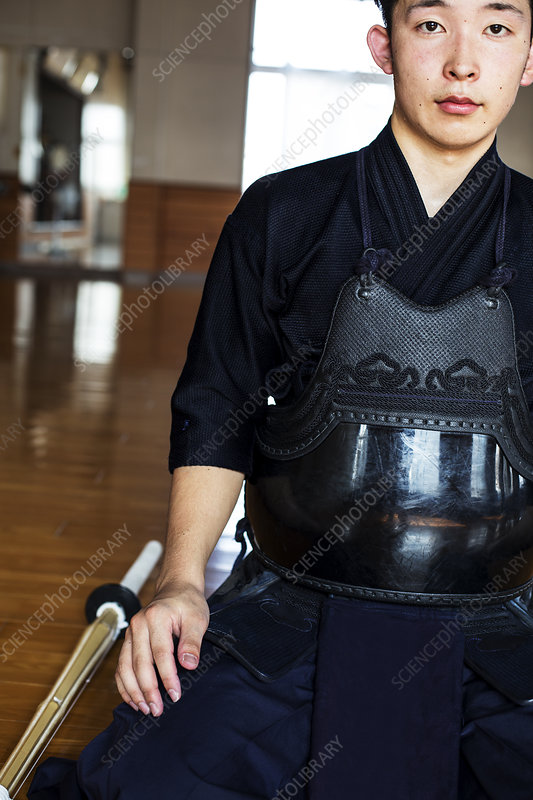 Male Japanese Kendo fighter kneeling on floor