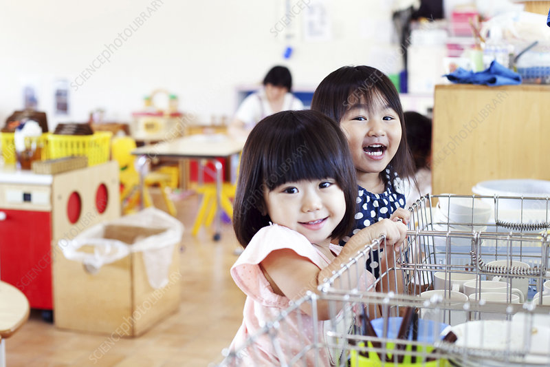 Two smiling girls in a Japanese preschool