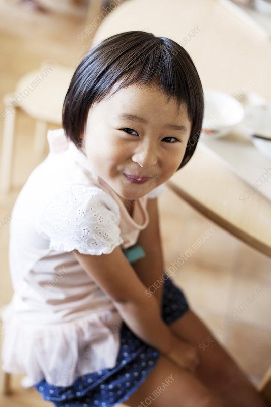 A smiling girl sitting on the floor in preschool