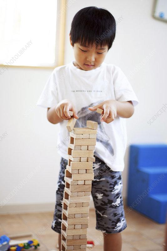 Boy playing with Jenga hardwood game in preschool