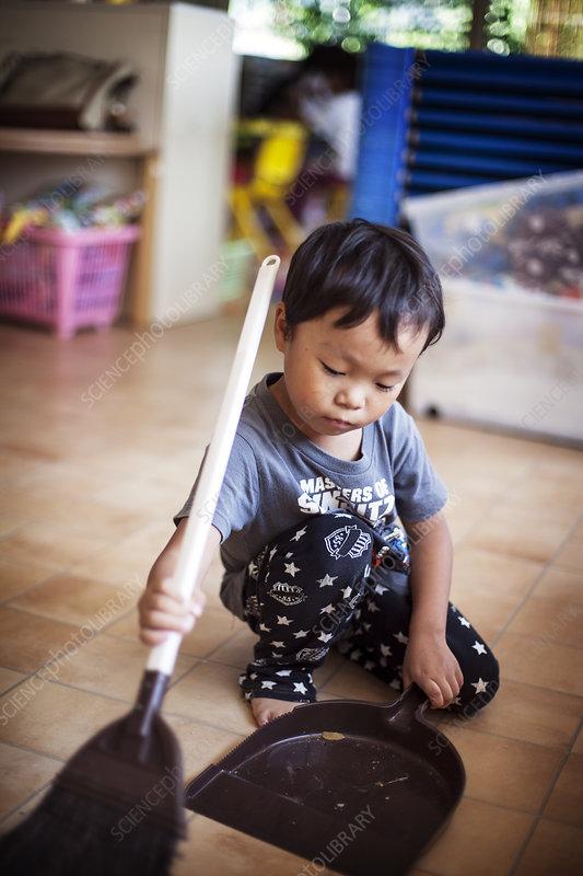 Girl using broom and dustpan in a Japanese preschool