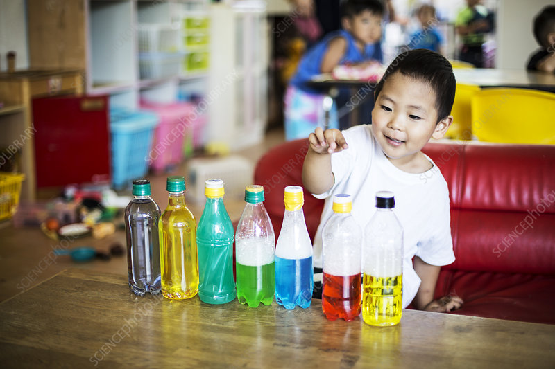Young boy playing with a selection of bottles
