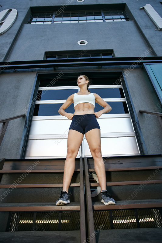 Female athlete standing on steps of industrial building