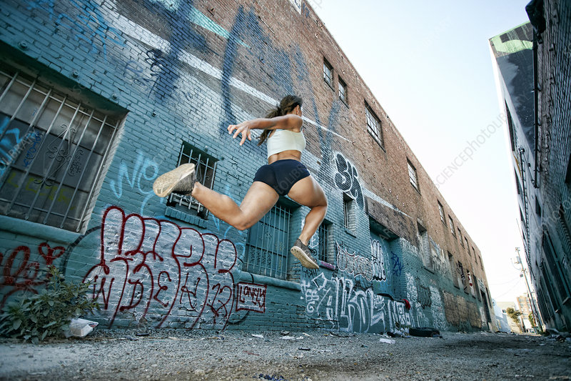 Female athlete running along urban sidewalk