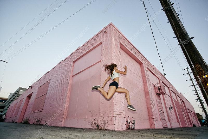 Female athlete running on sidewalk past pink building