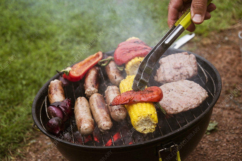 A person using tongs on food on a barbeque sausages