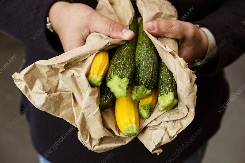 A woman holding a bunch of courgettes