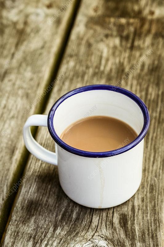 A white enamel mug of tea with a blue rim