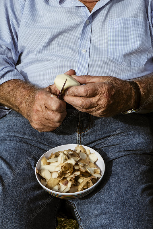 A man seated using a sharp knife to peel potatoes