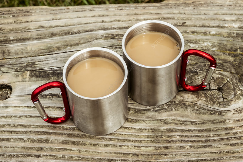 Two metal camping mugs of tea on a wooden table