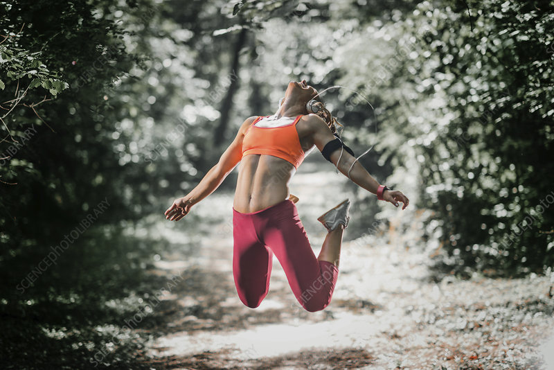 Female athlete jumping in a park