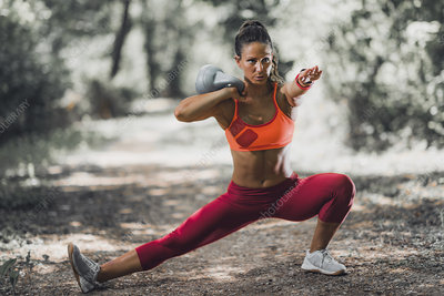 Woman exercising with kettlebell outdoors