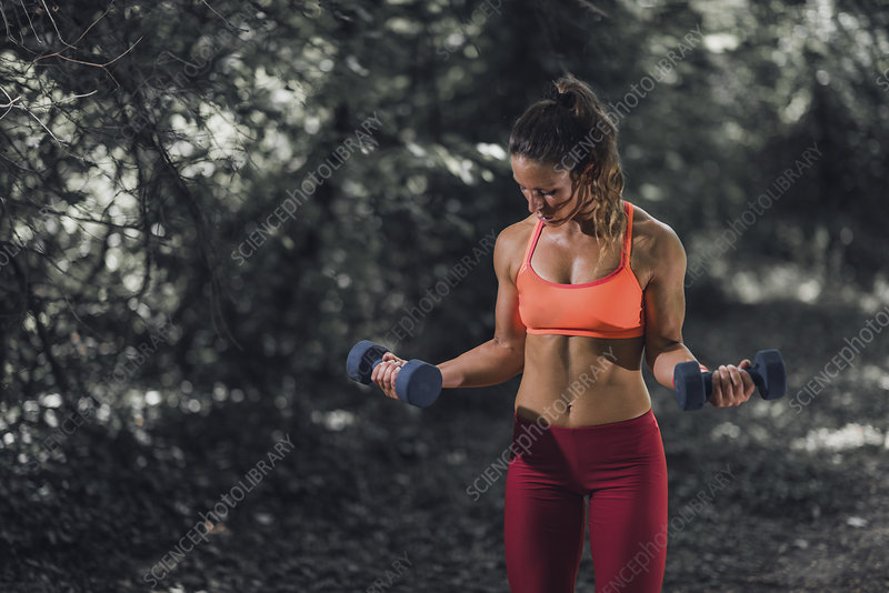 Woman exercising with dumbbells outdoors