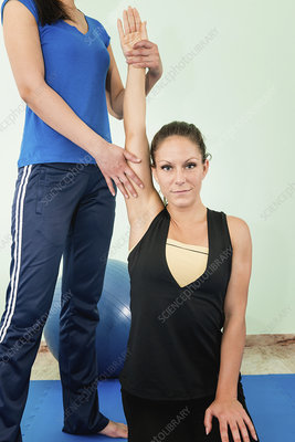 Physical therapist stretching woman's arm
