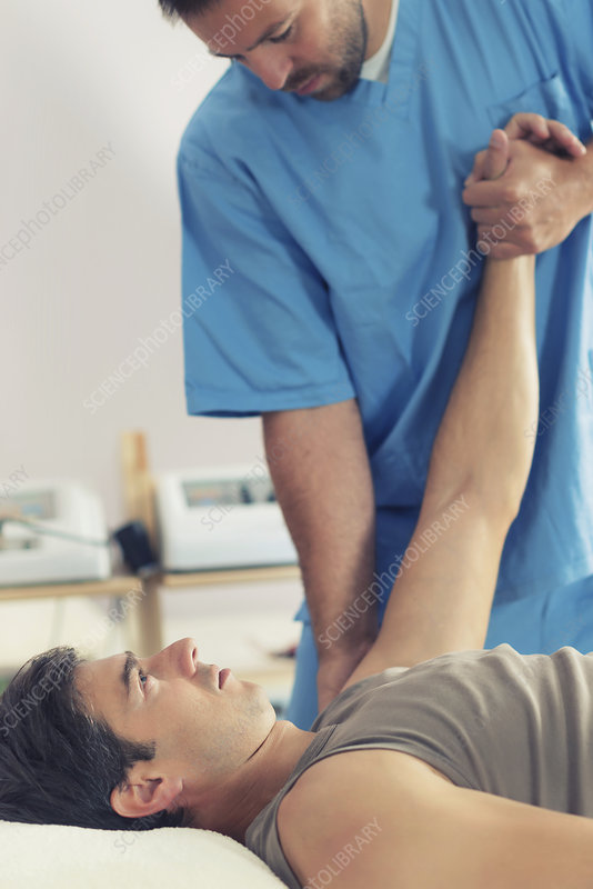 Physiotherapist stretching man's arm