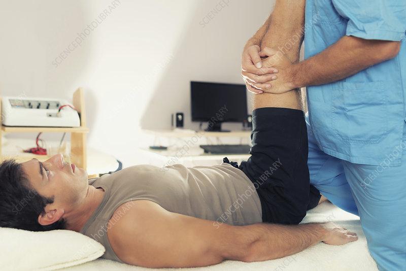 Physiotherapist stretching man's leg