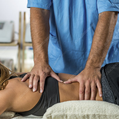Physiotherapist treating woman's back