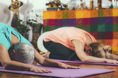 Senior woman in private yoga class