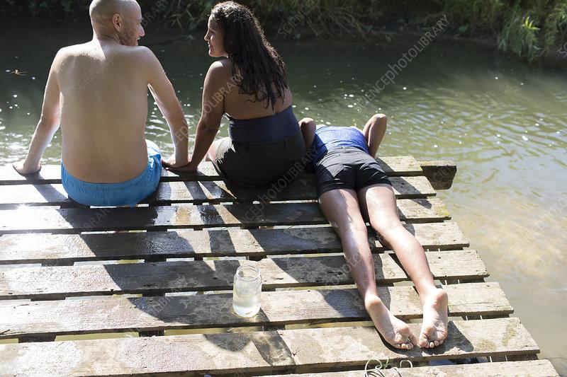 Family relaxing on dock at riverside