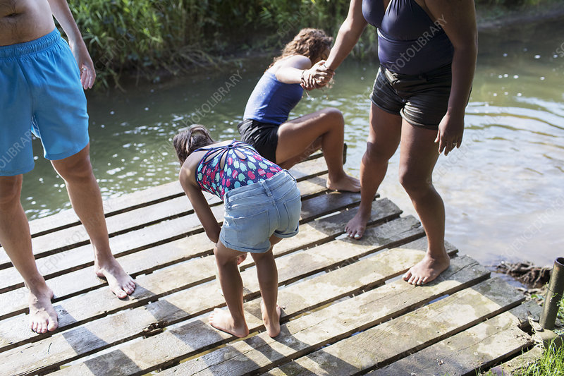 Family swimming, playing on riverside dock