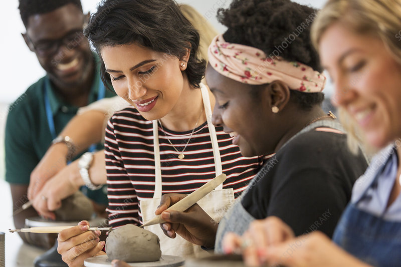 Women shaping clay in art class