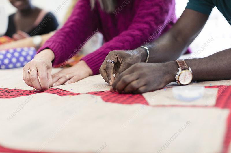 Fashion designers pinning sewing pattern