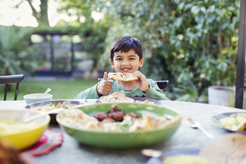 Portrait boy eating naan bread at patio table