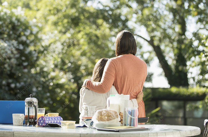 Affectionate mother and daughter on morning patio