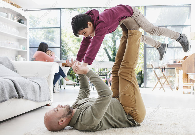 Father lifting son with legs on living room floor