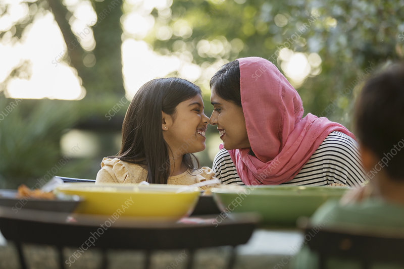 Affectionate mother in hijab rubbing noses