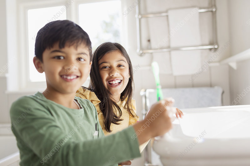 Portrait brother and sister brushing teeth in bathroom