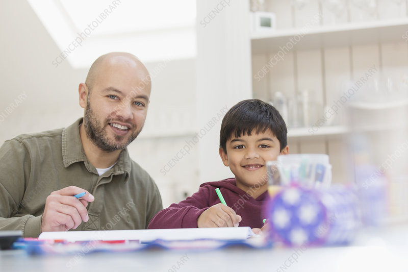 Portrait father and son colouring at table