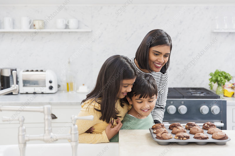 Mother and children baking chocolate muffins
