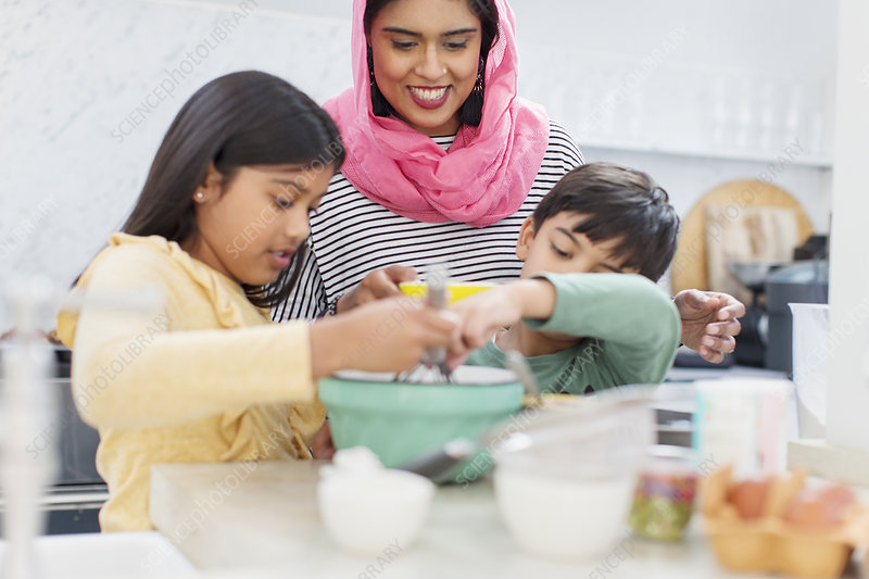 Mother in hijab baking with children in kitchen