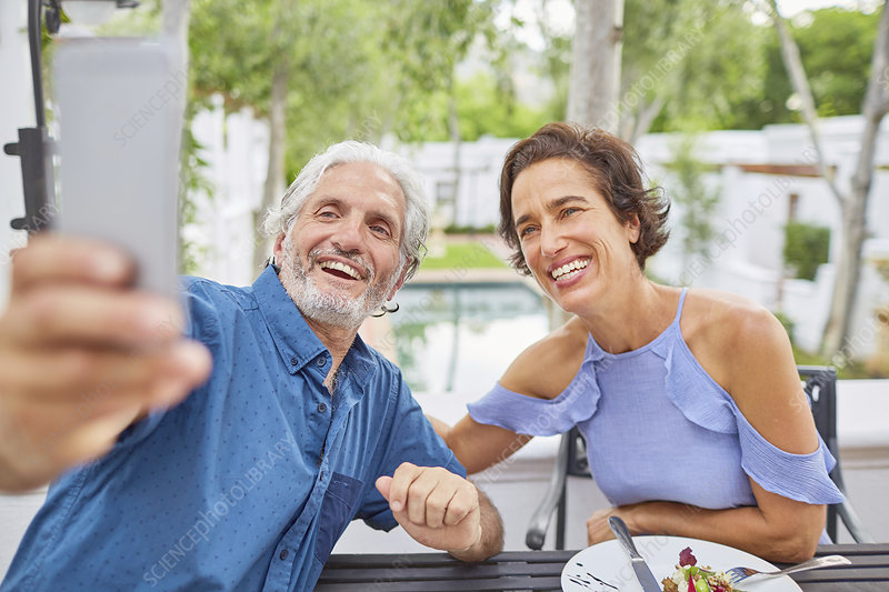 Mature couple taking selfie on hotel patio