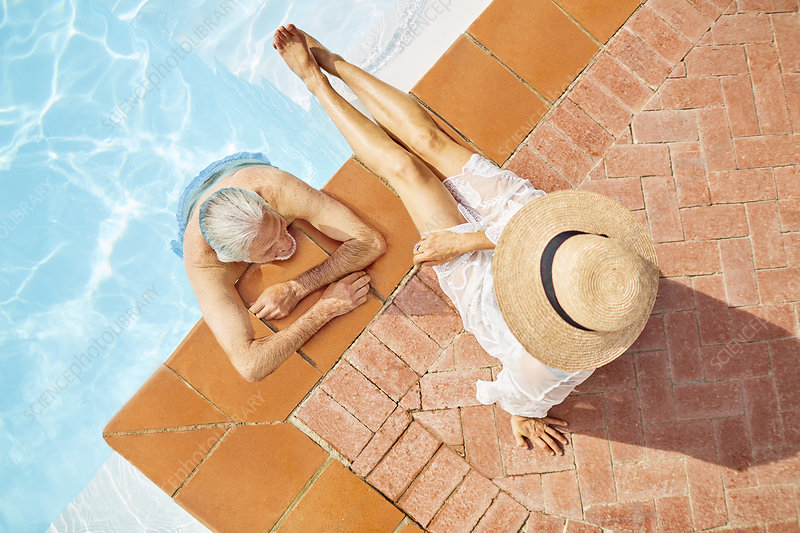 View from above mature couple relaxing at swimming pool