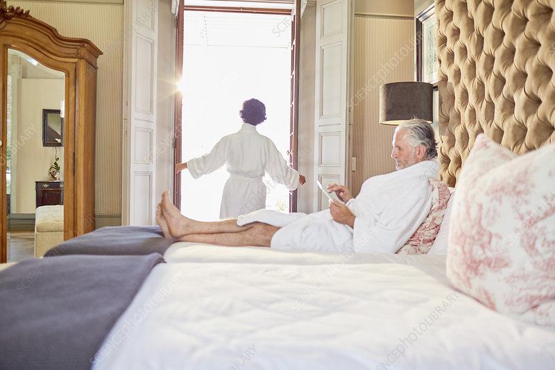 Mature couple in bathrobes relaxing in hotel bedroom