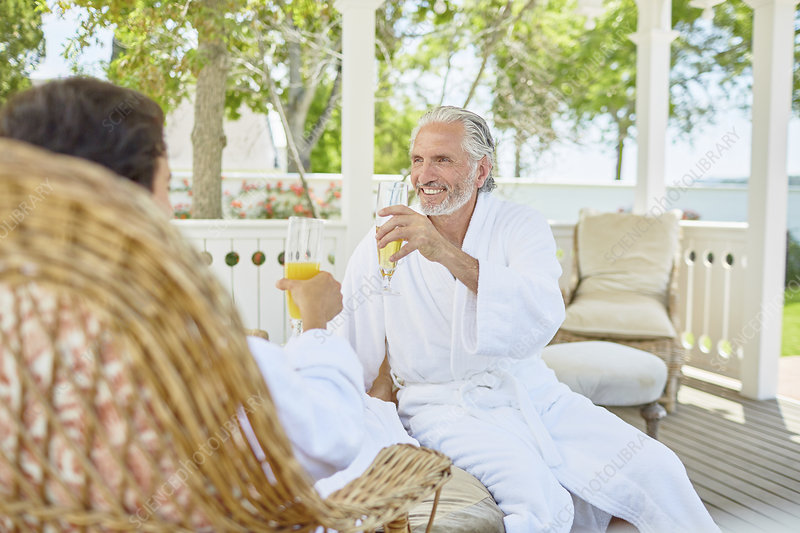 Mature couple in spa bathrobes drinking mimosas