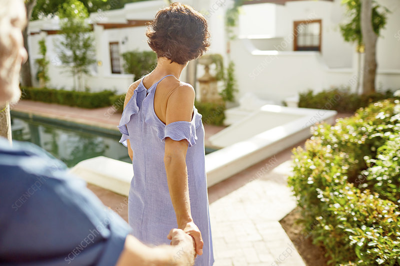 Couple holding hands, walking at poolside