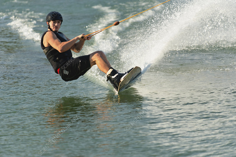 Wakeboarder cutting water surface